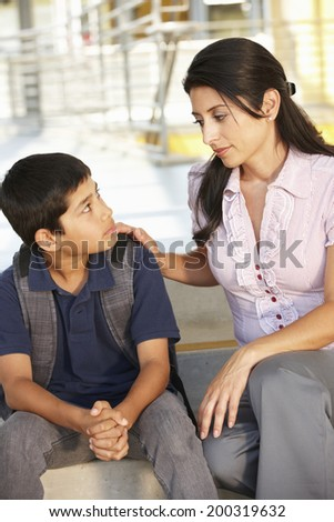 Unhappy Pre teen boy in school - stock photo