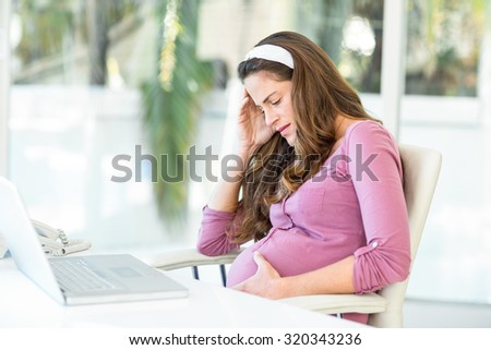 Unhappy pregnant woman with headache sitting on chair at desk in home office - stock photo
