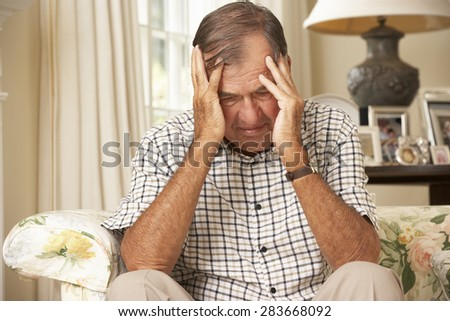 Unhappy Retired Senior Man Sitting On Sofa At Home - stock photo