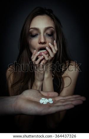 Unhappy sad girl going to use pills - stock photo