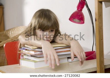 Unhappy sad  little girl studying at the desk - stock photo