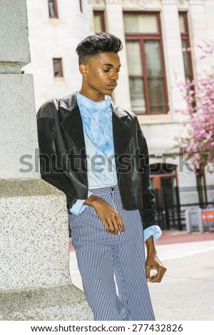 Unhappy school boy. A  young, 18 years old student, wearing black fashionable jacket, striped pants, blue dyed white shirt, standing by gate on campus, looking down, sad, thinking, lost in thought.  - stock photo