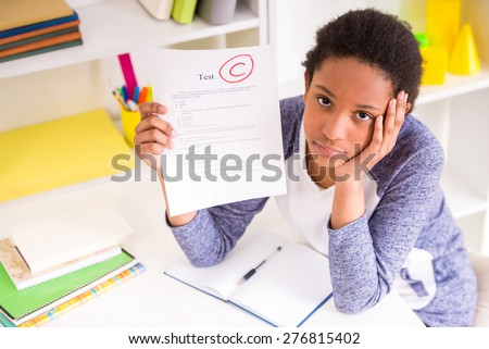 Unhappy schoolgirl sitting at the table and  showing  bad test results on colorful background. - stock photo