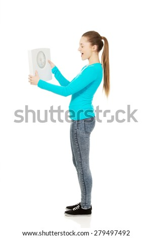 Unhappy teenage woman holding scale. - stock photo