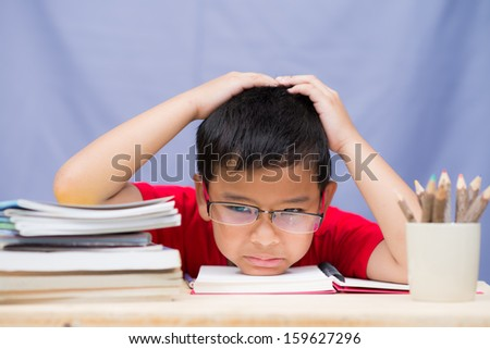 Unhappy tired boy doing his homework - stock photo