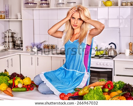 Unhappy tired woman in a blue apron preparing food at kitchen. - stock photo