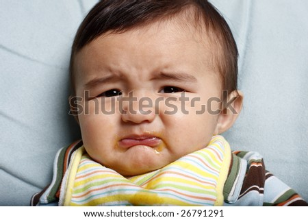 Unhappy toddler with food all over his face. - stock photo