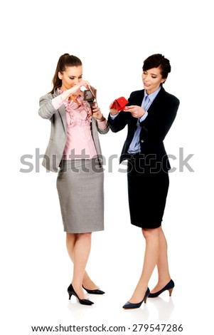 Unhappy two businesswomen with empty wallets. - stock photo