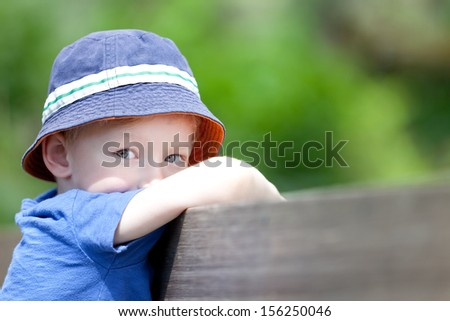 unhappy upset little boy outside - stock photo