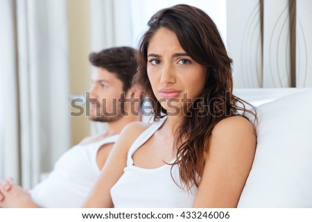Unhappy upset woman sitting in the bed with man on the back at home - stock photo