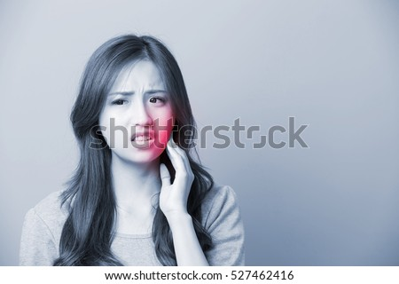 unhappy woman feel pain on her teeth isolated on gray background, asian