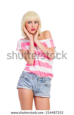 Unhappy woman. Grimacing blonde young woman holding hands on chin and looking away. Three quarter length studio shot isolated on white. - stock photo