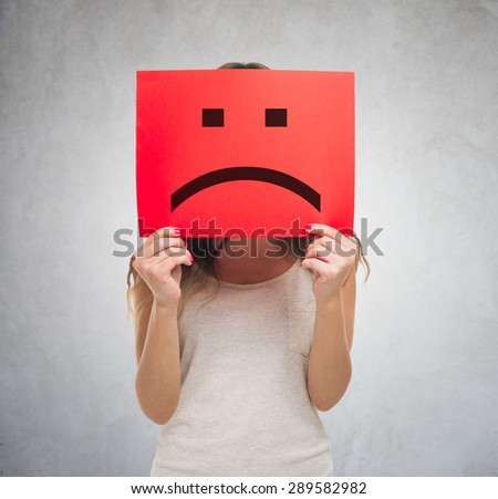 Unhappy woman holding a sad emoticon in front of his face - stock photo