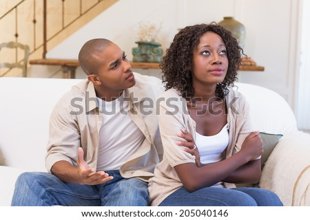 Unhappy woman not listening to his excuses at home in the living room - stock photo