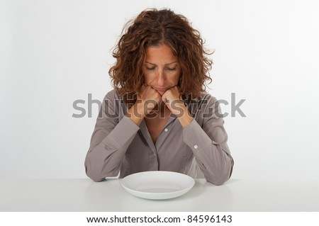 Unhappy woman sitting in front of an empty dish. Diet concept. You can place the food you prefer in the plate.