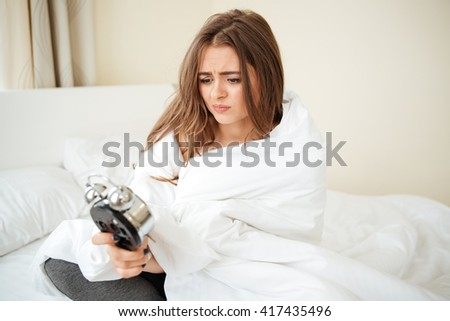 Unhappy woman sitting with alarm clock on the bed at home - stock photo