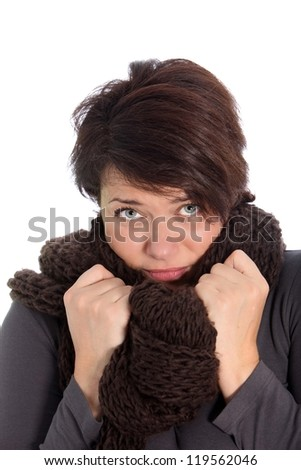 Unhappy woman suffering from the cold weather snuggling down inside her warm woolly knitted scarf with a despondent expression - stock photo