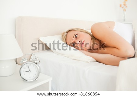 Unhappy woman waking up in he bedroom