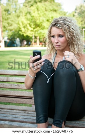 Unhappy woman with cellphone - stock photo