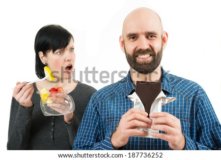 unhappy woman with fruit bowl looks angry at her chocolate eating boyfriend - stock photo