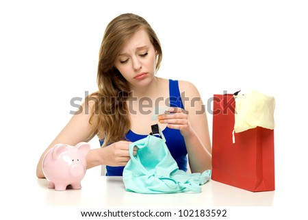 Unhappy woman with shopping bags and piggy bank - stock photo