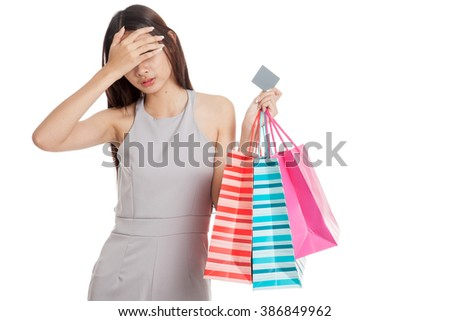 Unhappy  young Asian woman with shopping bags and credit card  isolated on white background - stock photo