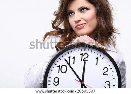 Unhappy young attractive woman with big clock on white.