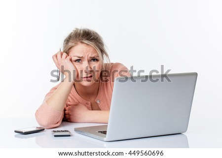 unhappy young blond woman leaning on her white sparse desk, looking disgusted and scared, working or studying hard on her computer, isolated white background