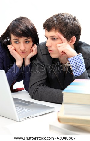 Unhappy young couple looking at laptop
