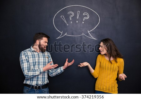 Unhappy young couple standing and quarreling over blackboard background - stock photo