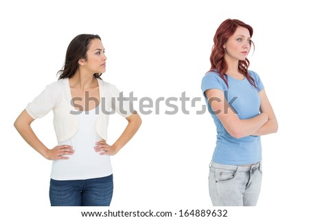 Unhappy young female friends not talking after argument over white background - stock photo