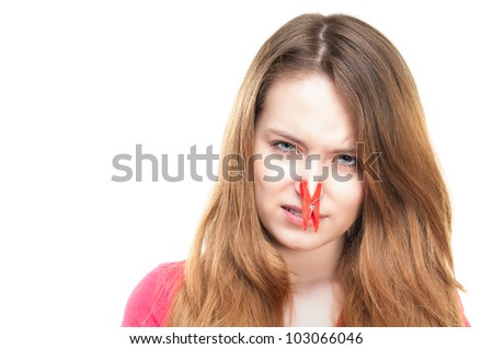Unhappy young girl feeling bad smell. Disgusted expression, red clothespin on her nose. Looking into the camera. Isolated on white background. - stock photo
