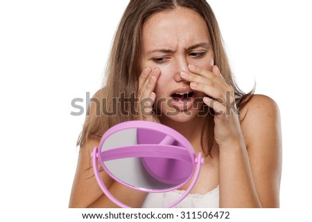 unhappy young girl looking at her pimple on her face in the mirror - stock photo