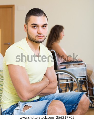 Unhappy young man and his girlfriend in invalid chair at home - stock photo
