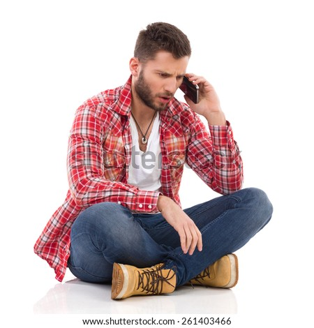 Unhappy young man in jeans and lumberjack shirt sitting on floor with legs crossed and using a smart phone. Full length studio shot isolated on white. - stock photo