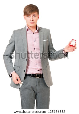 Unhappy young man in suit holding box with wedding ring, isolated on white background - stock photo