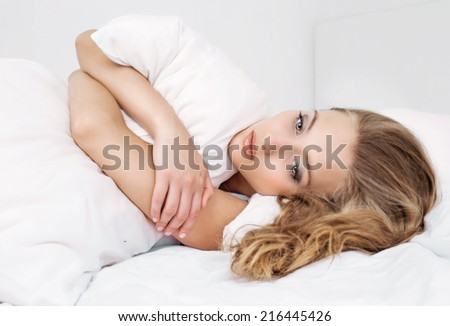 unhappy young woman in bed at home - stock photo
