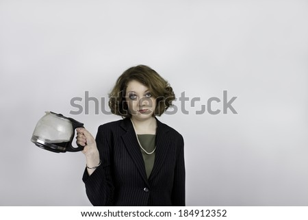 Unhappy young woman in business attire holding coffee pot - stock photo