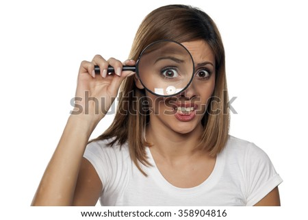 unhappy young woman looking through a magnifying glass - stock photo