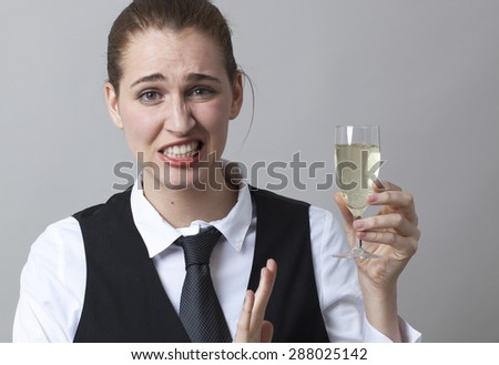 Unhappy young woman wearing uniform of wine waitress refusing glass of white bubbly wine - stock photo