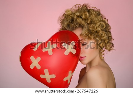 Unhappy young woman with ball in shape of heart on pink background - stock photo