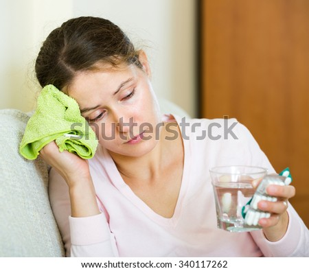 Unhappy young woman with headache and cold application at home