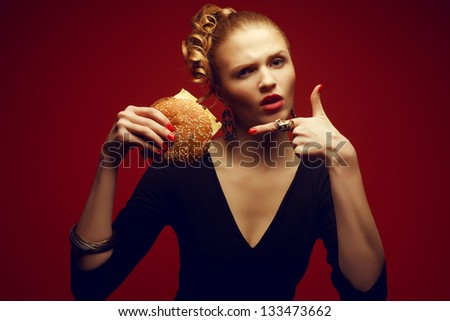 Unhealthy eating. Junk food concept. Guilty pleasure. Portrait of a fashionable model holding burger and pointing on it with index finger. Perfect accessories, hair, skin, make-up and manicure. - stock photo