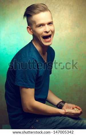 Unhealthy eating. Junk food concept. Portrait of fashionable young man holding popcorn in his hands and screaming. Great haircut and healthy skin. Disgusted expression on face. Copy-space. Studio shot - stock photo