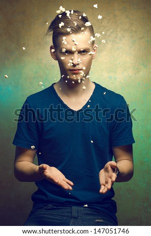 Unhealthy eating. Junk food concept. Portrait of fashionable young man making popcorn flying over golden background. Great haircut and healthy skin. Studio shot  - stock photo