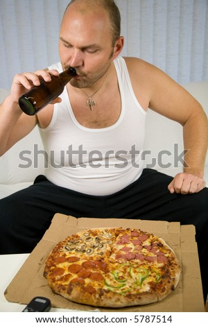 Unhealthy fat man sitting on the couch with beer and pizza