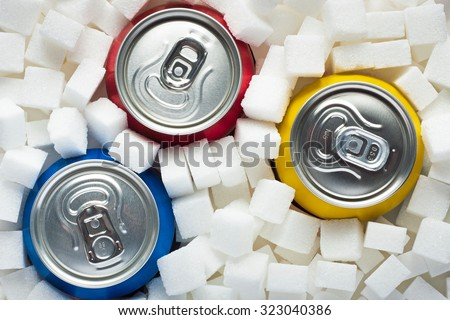 Unhealthy food concept - sugar in carbonated drinks. Sugar cubes as background and canned drinks  - stock photo