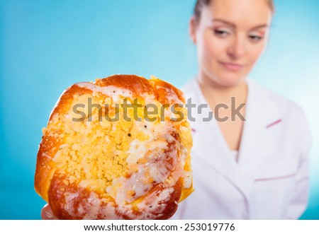 Unhealthy nutrition overweight concept. Nutritionist saying no to sugary dessert. Woman doctor dietician holding sweet bun recommending non sugar diet on blue - stock photo