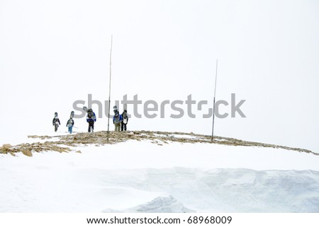 Unidentifiable Snowboarders Hiking Across a Frozen Landscape - stock photo