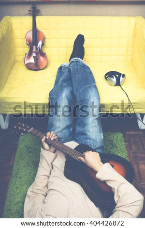 unidentified asian man playing guitar & lying on the floor, violin and headphone on yellow seat + art filter for music lover or cozy living lifestyle concept - stock photo